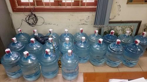 """Sau khi đóng nước vô bình, các đối tượng chuyển """"sản phẩm"""" về nơi ở của Thành và nhân viên tại ngõ 202 Định Công Hạ để dán nhãn và Capseal (màng co) sau đó mang đi tiêu thụ."""